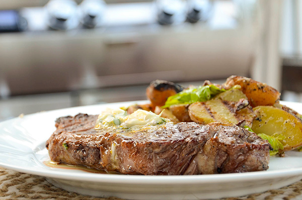 grilled steak with butter and potatoes